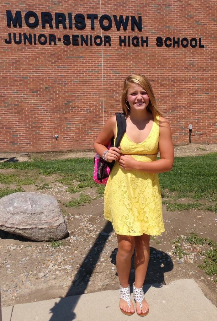 Greenley Goedde. a junior at Morristown Junior-Senior High School, smiles. She is in a yellow dress with white sandals and a pick backpack.
